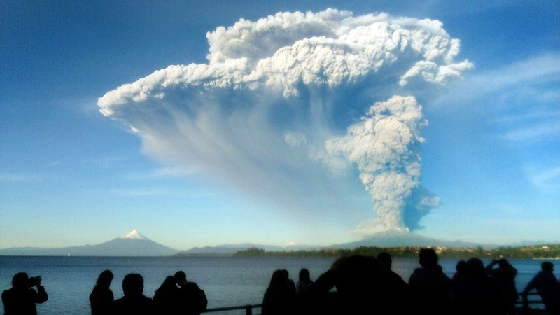People watch from Puerto Varas, southern Chile, a high column of ash and lava spewing from the Calbuco volcano, on April 22, 2015. Chile's Calbuco volcano erupted on Wednesday, spewing a giant funnel of ash high into the sky near the southern port city of Puerto Montt and triggering a red alert. Authorities ordered an evacuation for a 10-kilometer (six-mile) radius around the volcano, which is the second in southern Chile to have a substantial eruption since March 3, when the Villarrica volcano emitted a brief but fiery burst of ash and lava. AFP PHOTO/GIORDANA SCHMIDT  BEST QUALITY AVAILABLE