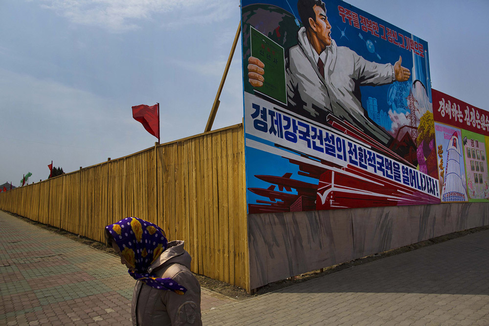 """A North Korean woman walks past the outer wall of a construction site where a propaganda billboard depicting the launch of North Korean rockets in Pyongyang, North Korea on Saturday, April 12, 2013. The billboard reads """"Lets Open Up An Era To A Strong Economic Country."""" (AP Photo/David Guttenfelder)"""