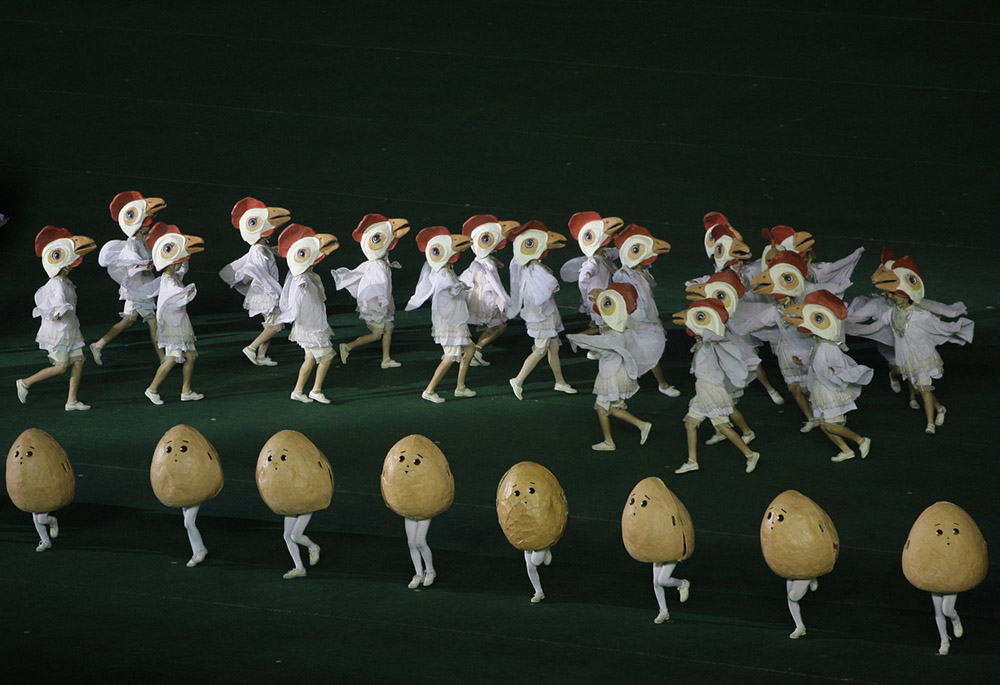 """North Koreans, dressed as chickens and eggs, dance at a stadium in Pyongyang, North Korea during a """"mass games"""" performance Wednesday, Sept. 17, 2008. The section of the performance was about agricultural self reliance. (AP Photo/David Guttenfelder)"""