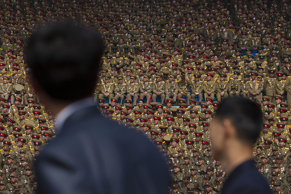 Two North Korean officials look up at a crowd of military members seated in a stadium in Pyongyang during a mass meeting called by the Central Committee of North Korea's ruling party on Saturday April 14, 2012. North Korea will mark the 100-year birth anniversary of the late leader Kim Il Sung on Sunday April 15. (AP Photo/David Guttenfelder)