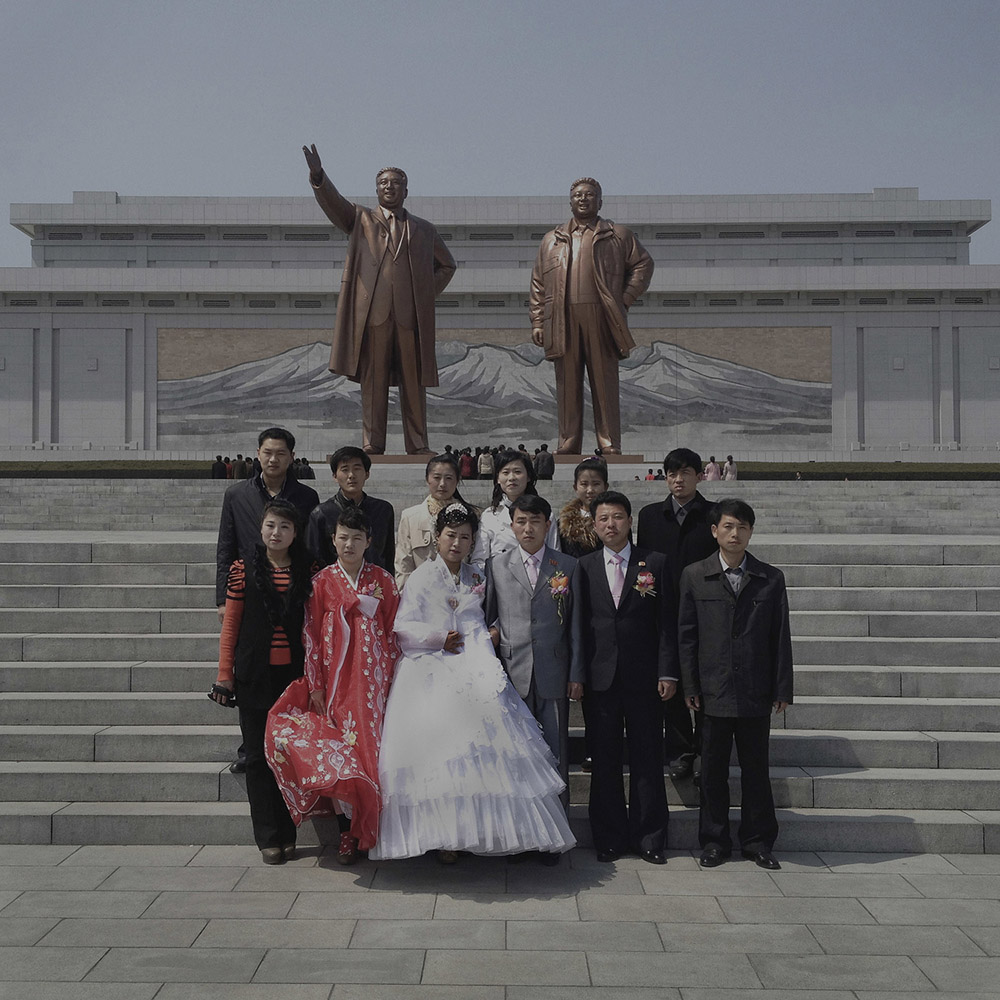 A North Korean wedding party pose for photos in front of statues of the late leaders Kim Jong Il and Kim Il Sung in Pyongyang.
