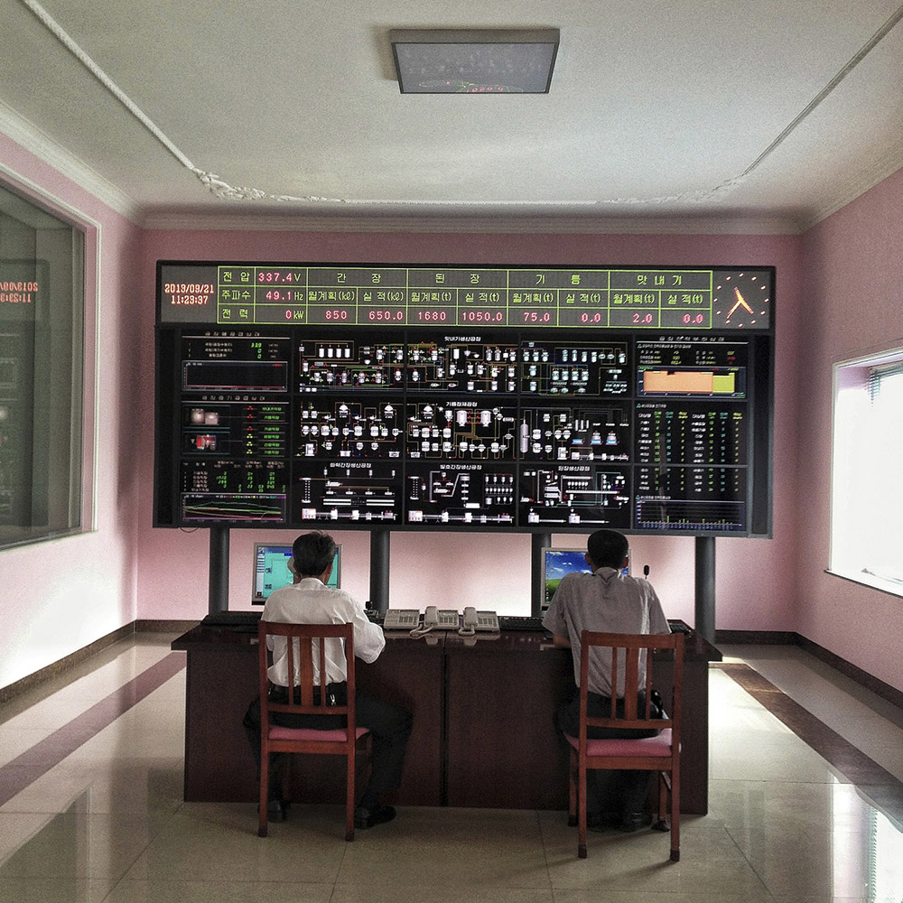 North Korean men sit behind a large electronic board that officials said displayed the working information of a food processing factory in Pyongyang.