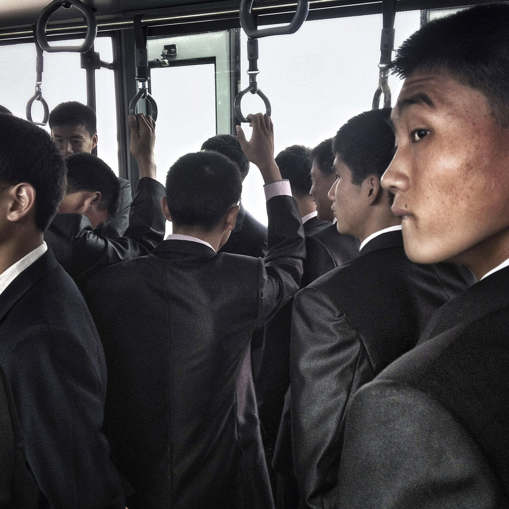 North Korean men stand as they ride a airport shuttle on their way to the North Korean Air Koryo flight from Pyongyang to Beijing waiting on the tarmac.