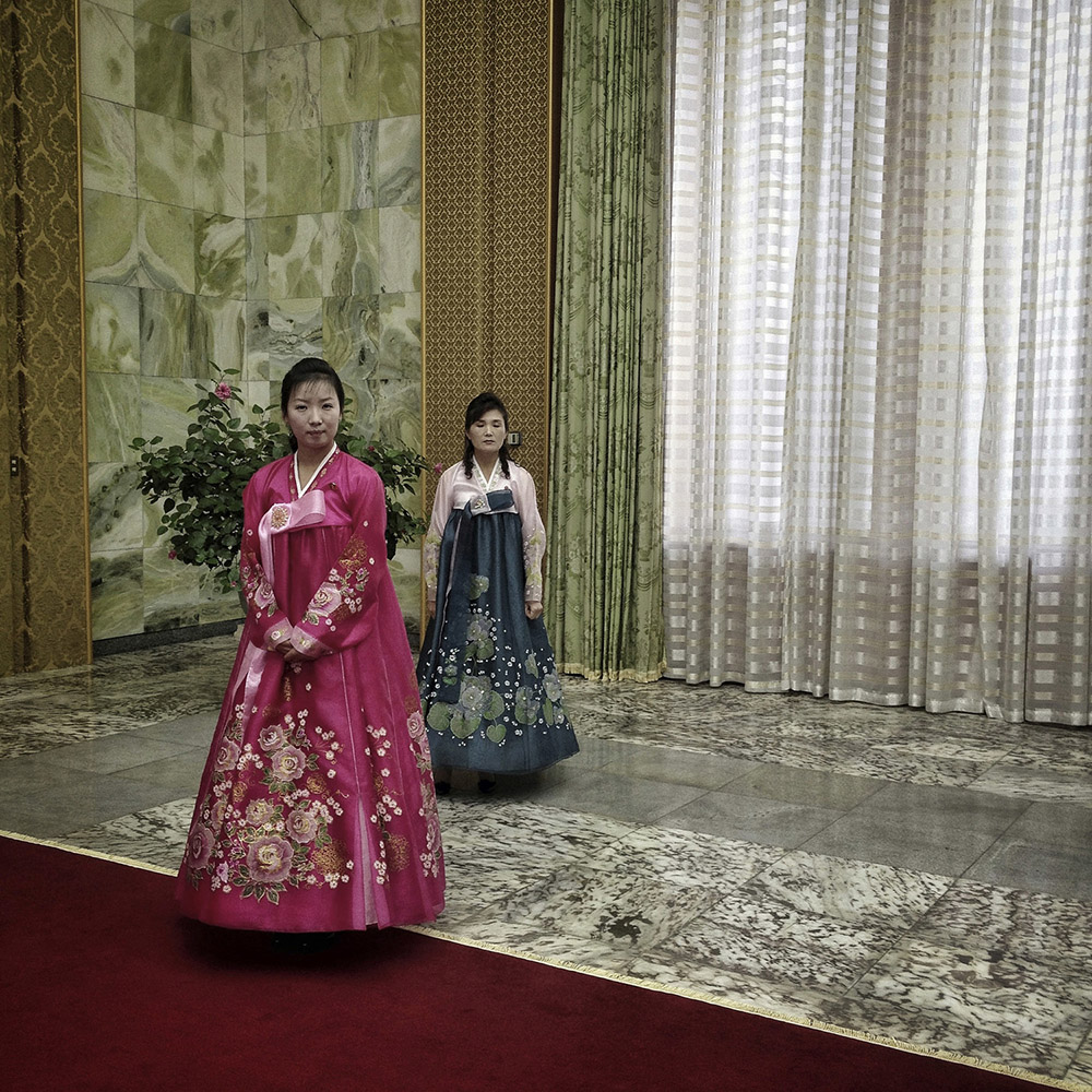 Two North Korean women in traditional dresses stand in the red-carpeted entry to the Mansudae Assembly Hall in Pyongyang to greet visitors coming to meet the the head of the Presidium of the Supreme People's Assembly Hall of North Korea, Kim Yong Nam.