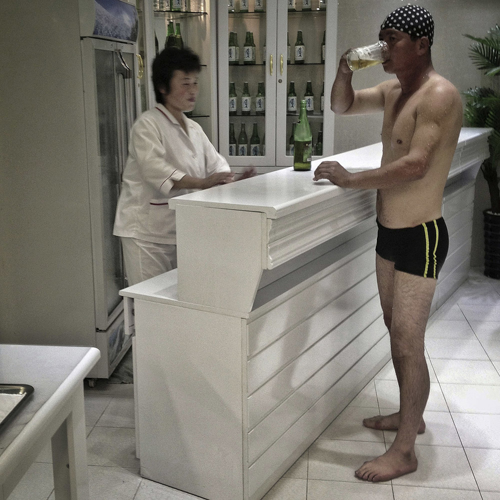 A North Korean man drinks beer in his swimsuit and cap at an indoor poolside bar that officials said was built as a recreational facility for workers at a food processing factory in Pyongyang.