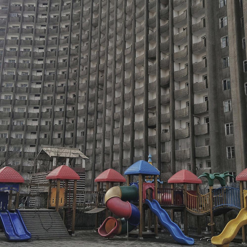 Playground equipment stand on a kindergarten school yard beneath an apartment housing building in Pyongyang, North Korea.