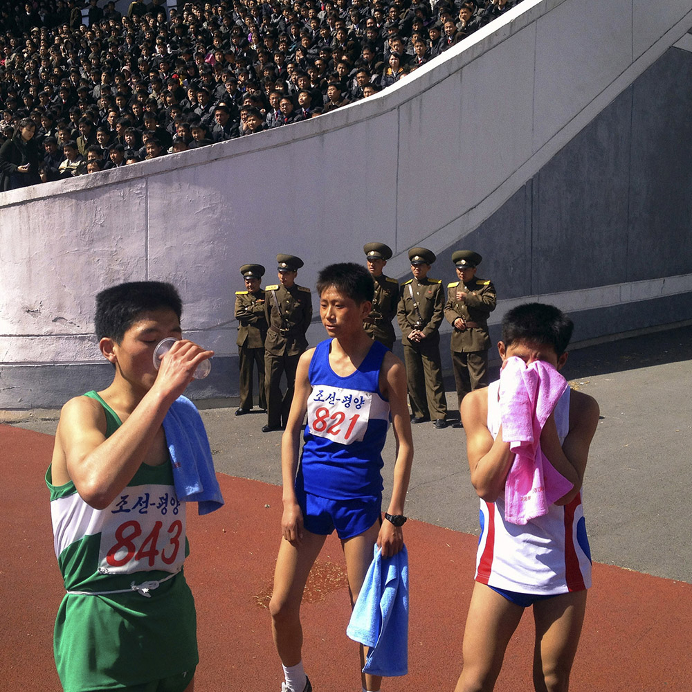 North Korean runners rest at the finish line of the 26th Mangyongdae Prize Marathon in Pyongyang, North Korea.