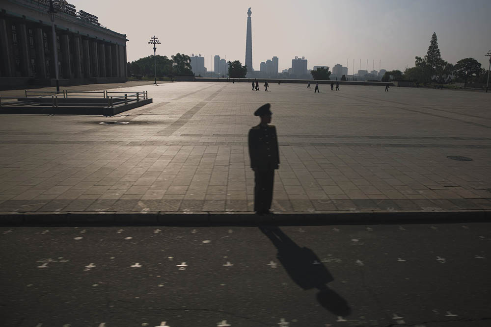 A North Korean soldier stands on the curb in front of Kim Il Sung Square in Pyongyang. The painted grid markings on the street and square are added to indicate standing spots and marching steps placement during mass parades held in Pyongyang.  Photo by David Guttenfelder