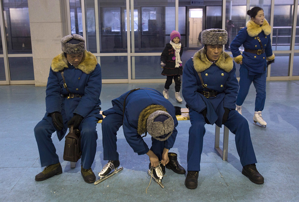 An off duty North Korean traffic policeman laces up ice skates as his colleagues look on at an ice skating rink in Pyongyang, North Korea Friday, Jan. 11, 2013. (AP Photo/David Guttenfelder)