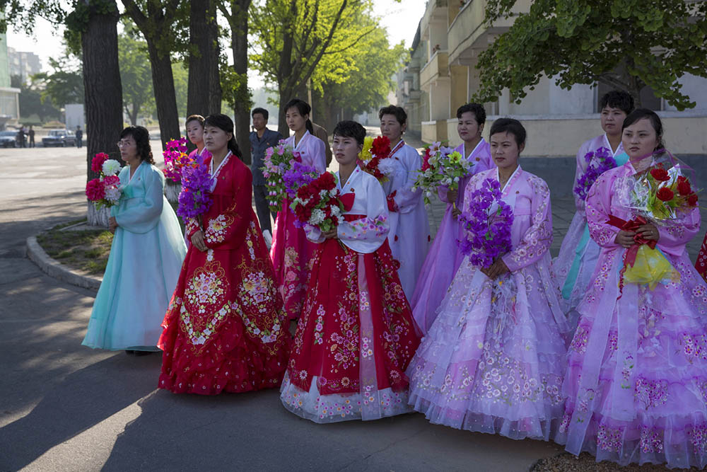 North Korean women gather early in the morning on the street in central Kaesong, North Korea before a march calling for peace and reunification on the Korean peninsula organized for a group of visiting international women peace activists.  Photo by David Guttenfelder