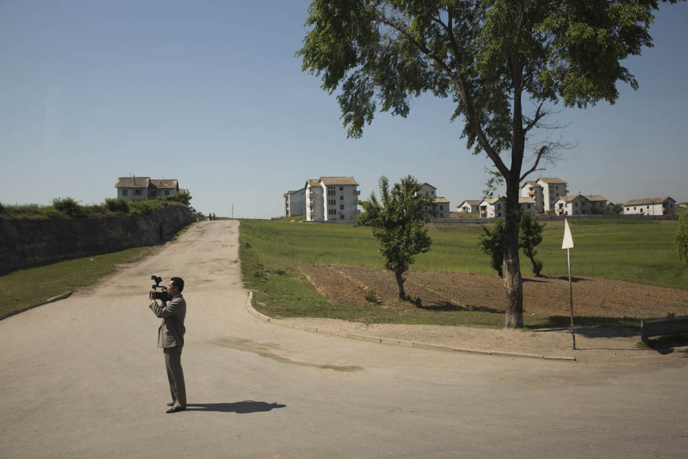 A North Korean television journalist films the buses of visiting international women peace activists as they pass by near the Demilitarized zone separating the two Koreas. Photo by David Guttenfelder