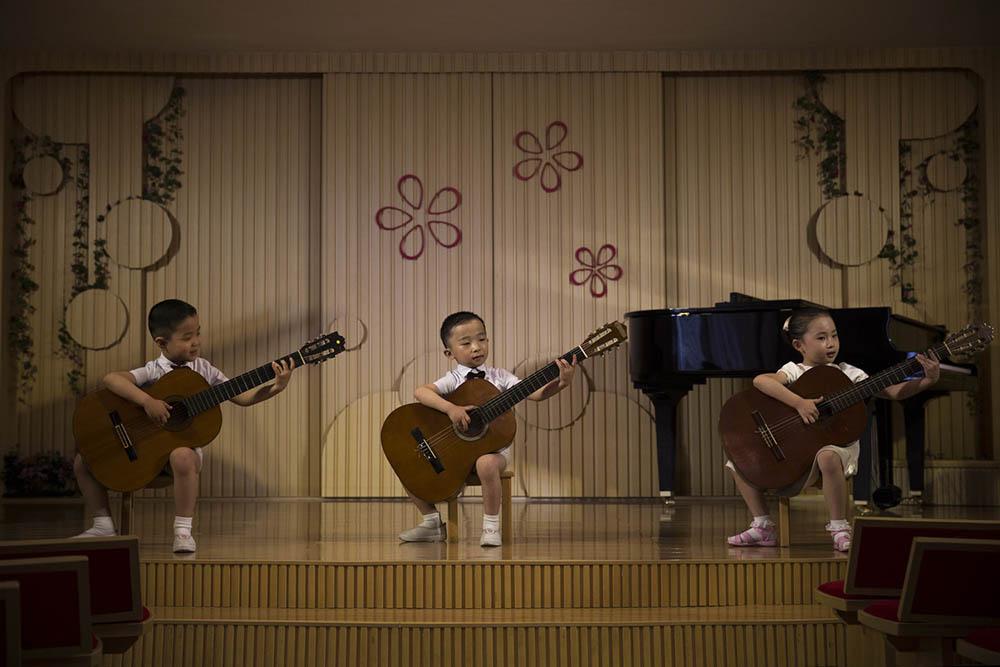 North Korean  boys play acoustic guitars during a performance at the Pyongyang Kyongsang Kindergarten. Photo by David Guttenfelder