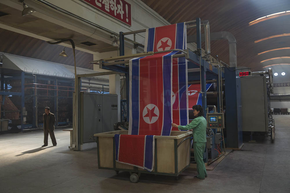 A textile factory worker guides rolls of North Korean flags into a basket at the Kim Jong Suk Pyongyang Textile Factory. Photo by David Guttenfelder