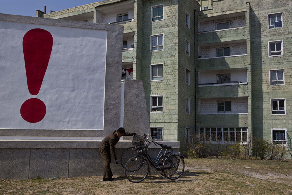 A North Korean man checks his bicycle next to a painted exclamation point on a propaganda billboard on Wednesday April 24, 2013 in Kaesong, North Korea, north of the demilitarized zone which separates the two Koreas. (AP Photo/David Guttenfelder)