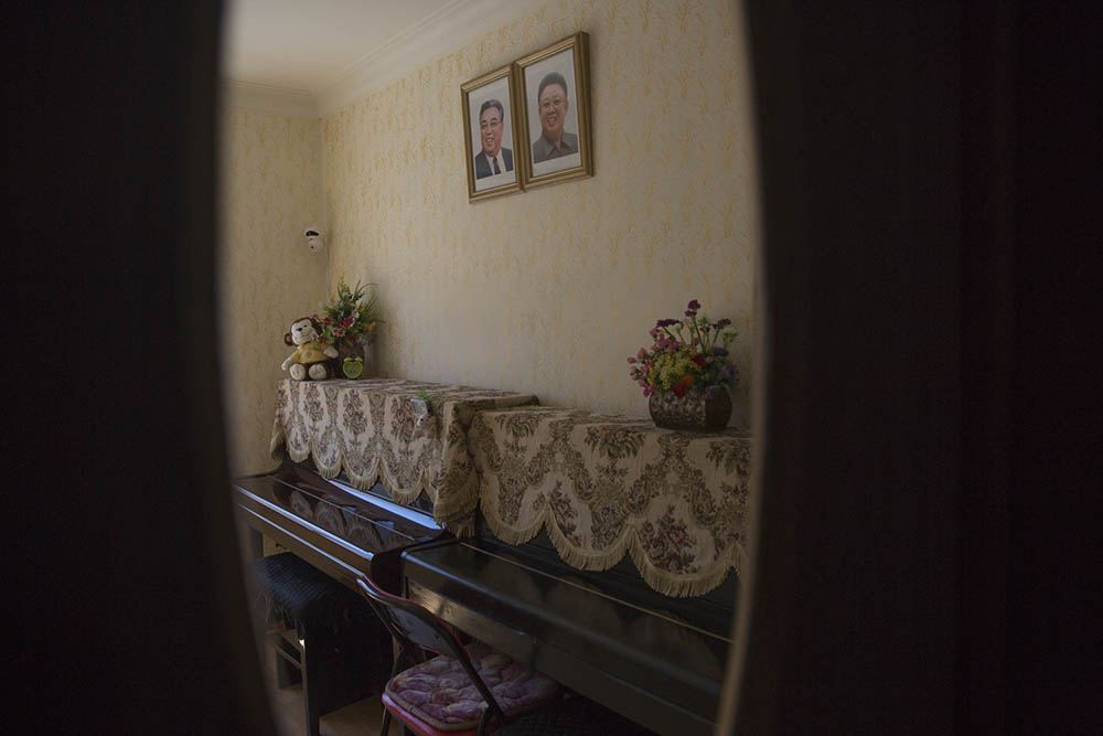 Portraits of the late leaders Kim Il Sung, left,  and Kim Jong Il hang over two doily-draped pianos inside the Pyongyang Kyongsang Kindergarten. Photo by David Guttenfelder