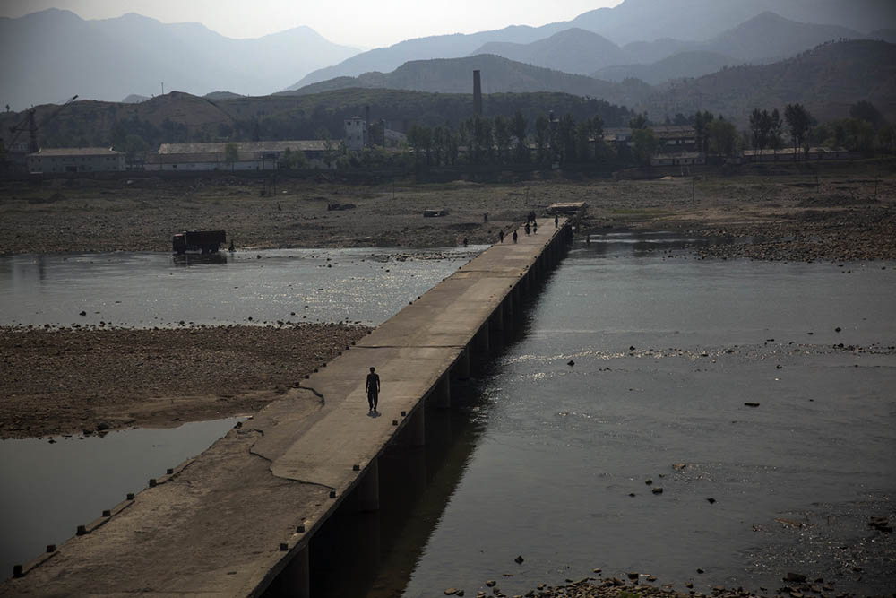 A man uses a bridge to cross a river in North Korea's Phyonganbuk-Do province in the northwest of the country. Photo by David Guttenfelder