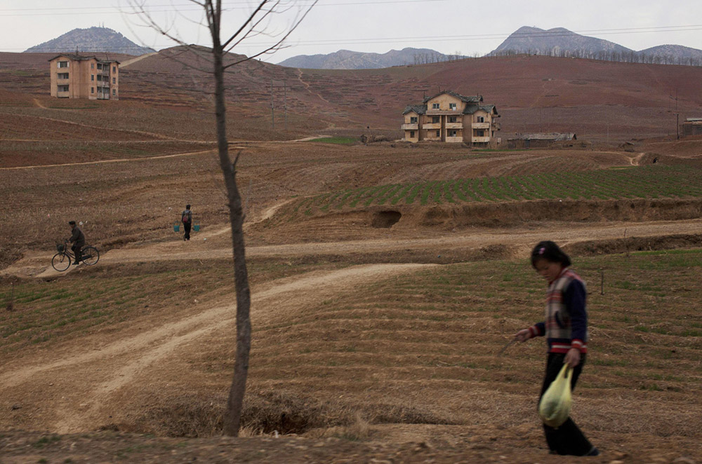 North Koreans go about their daily routines south of Pyongyang along the highway to the southern city of Kaesong.