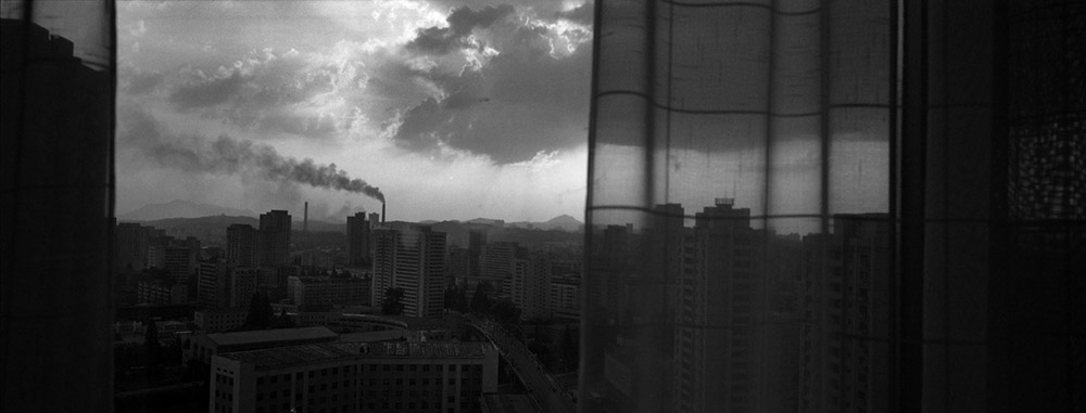 The sun sets over Pyongyang, North Korea, behind the curtained window of a downtown hotel room.