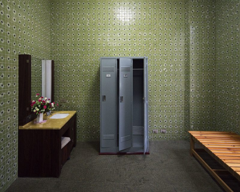 Dressing room of a private sauna at the Changgwang-won health complex, featuring beautiful green tile work with black floor, matching the unique vintage tones of the city.