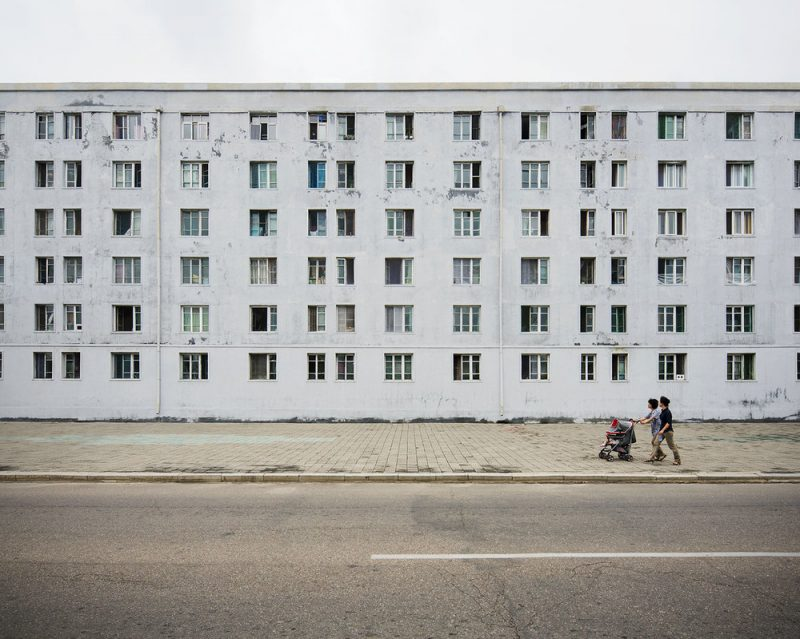 Old building with passers by in central Pyongyang. The gray, minimal, textured facade with grid-like windows was built by the Russians while helping North Korea to rebuild its capital after the Korean war. It seemingly has seen many winters, just like the people of this nation.
